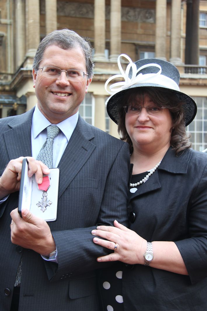 Robert and Helen Mitchell pose proudly outside Buckingham Palace after receiving his MBE.
